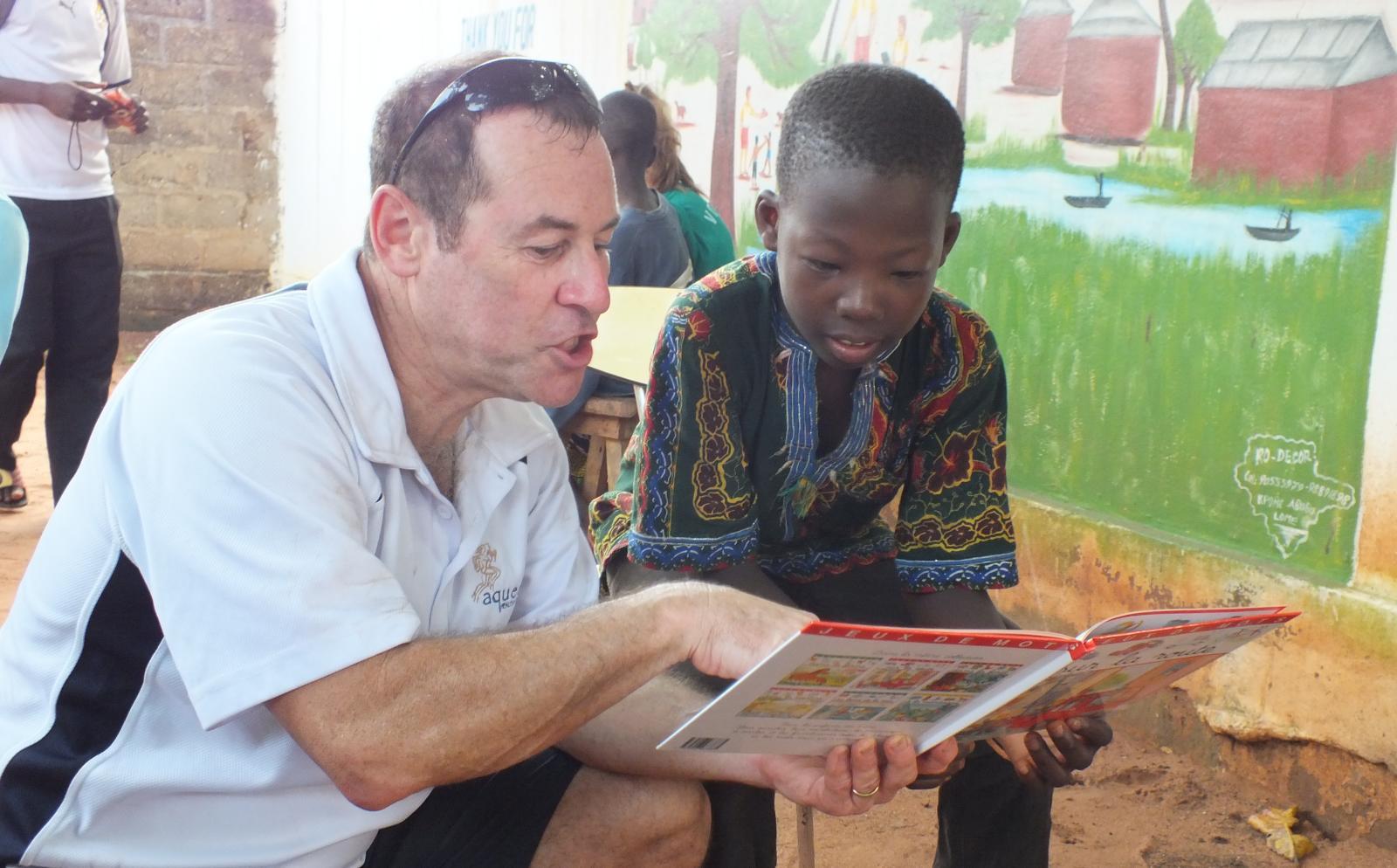 Un volontaire lit un livre à un enfant dans le cadre d'une mission de volontariat pour seniors
